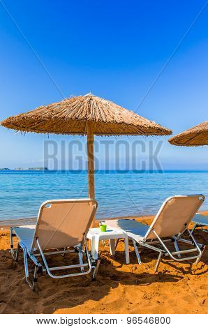 Straw Umbrellas And Sunbeds On A Red Sand Beach And Turquoise Water.