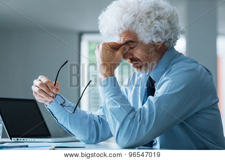 Stressed Businessman Sitting At Office Desk