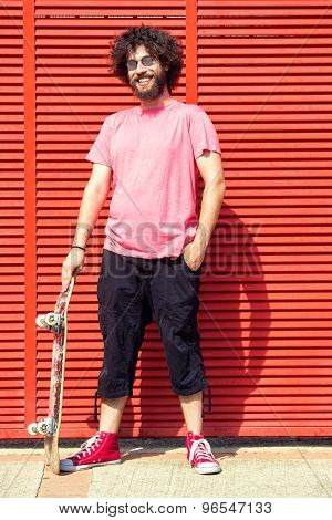 Man with skateboard on red background
