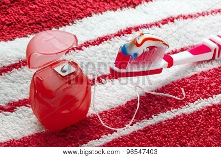 Dental floss and toothbrush on a red towel.