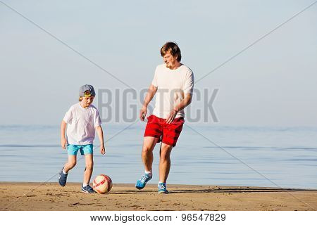 Happy father and son play soccer or football on the beach