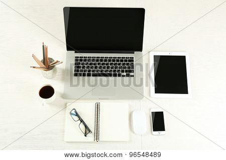 Laptop with tablet and smart phone on Workplace top view
