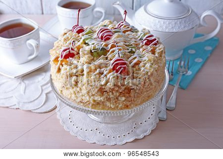 Butter cake with cherries on stand and table setting, on color wooden background