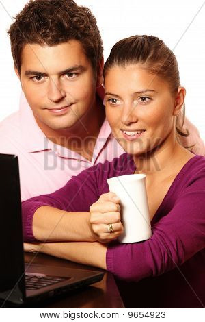 Young Married Couple Working On Laptop Together