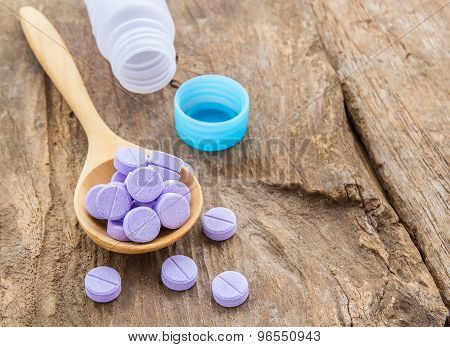 Medical Pills In Wooden Spoon On Wooden Table