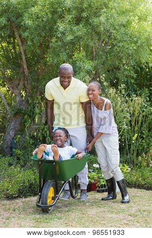 Happy smiling couple playing with wheelbarrow and their son at home in garden