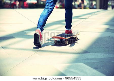 young skateboarder legs riding on skateboard on city