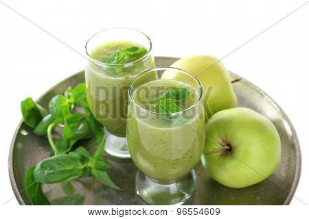 Glasses of green healthy juice with basil and apples on metal tray close up