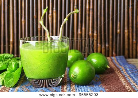Glass of green healthy juice with spinach and limes on wooden background