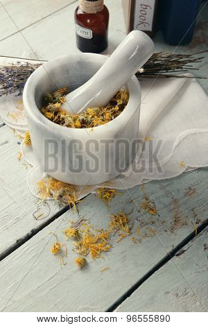 Different dried herbs and mortar on table close up