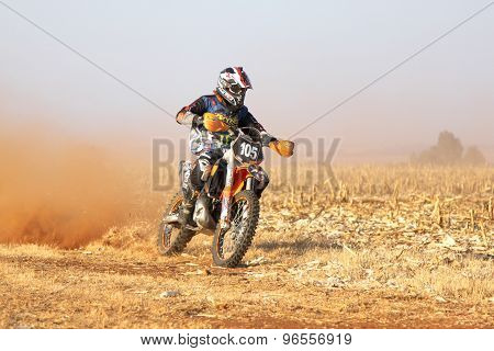 Motorbike Kicking Up Trail Of Dust On Sand Track During Rally Race.