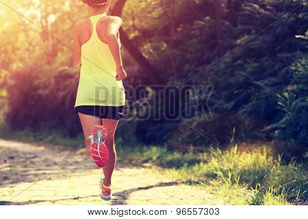 Runner athlete running on forest trail.
