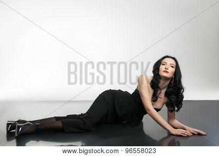 Gorgeous lady wearing black corset and skirt lying on the floor