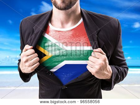 Businessman stretching suit with South African Flag with beach background