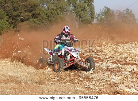Quad Bike Kicking Up Trail Of Dust On Sand Track During Rally Race.