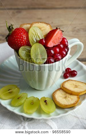 Cup of dessert with fresh fruits on wooden table, closeup