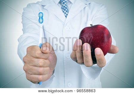 a dentist showing a toothbrush and an apple depicting the importance of tooth brushing and eating apples for a good dental health