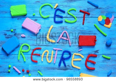 the sentence cest la rentree, back to school in french, written with modelling clay of different colors on a blue rustic wooden background