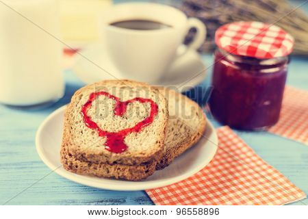 jam forming a heart on a toast, on a rustic blue wooden table, with a cross-process effect