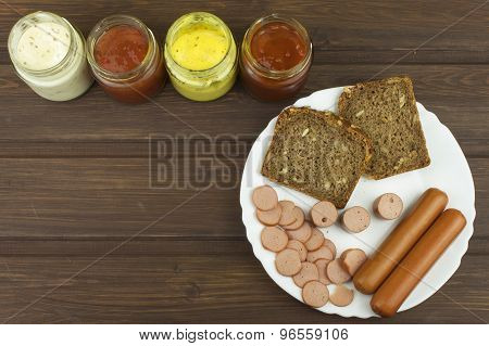 Poultry sausages on a wooden table, preparing home-made snacks.