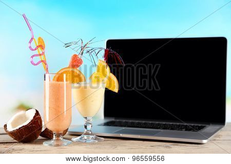 Laptop and glasses of summer cocktails on wooden table, on bright blurred background