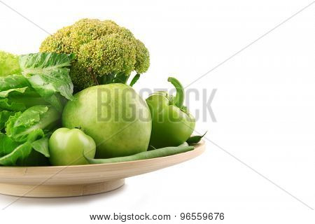 Fresh green food in wooden plate isolated on white