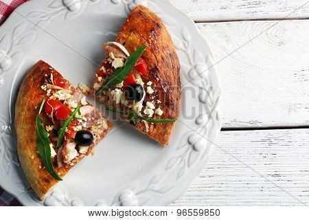 Pieces of homemade pizza on plate, on color table background