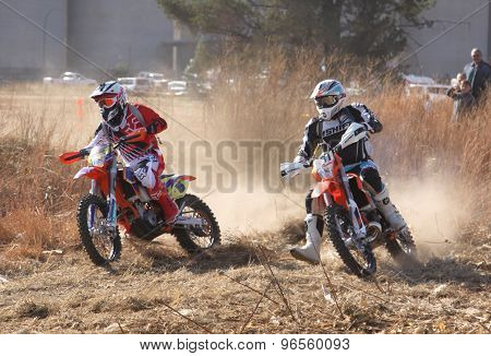 Two Motorbikes Kicking Up Trail Of Dust On Sand Track During Rally Race.
