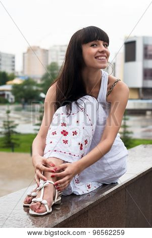 Attractive smiling woman sits over city background