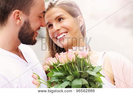 A picture of a young romantic couple with flowers in the city