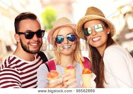 A picture of a group of friends eating ice-cream in the city
