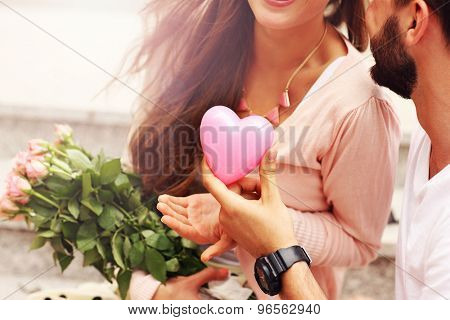 A midsection of a romantic couple with flowers and heart