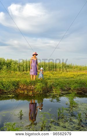 Little Girl Sitting With Her Mother Near The Lake