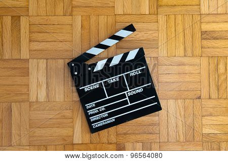 Movie Clapper Board On Wooden Floor