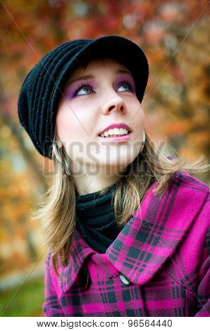 Smiling girl in pink coat in the fall