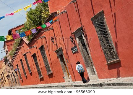 Mexican Man Passing By Colorful Buildings In Zocalo Street Of San Miguel De Allende