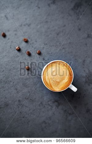 Cup of cappuccino on a stone surface