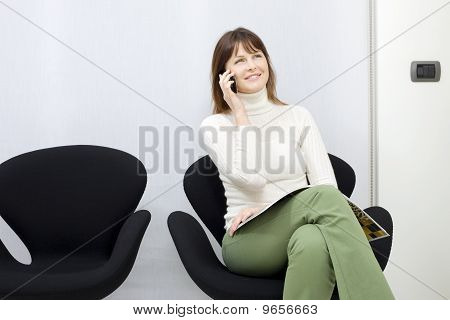 young caucasian woman on the mobile sitting in the waiting room for doctors