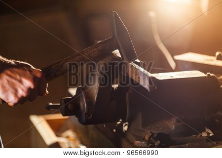 Closeup hands of man working holding hammer in workshop