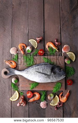 Dorado fish and other ingredients on wooden table, top view