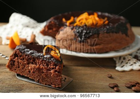Cake with Chocolate Glaze and orange on plate, on wooden table, on dark  background