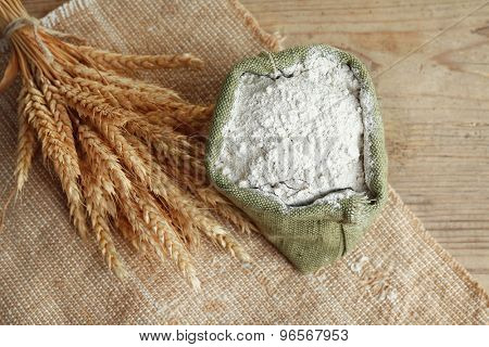 Whole flour in burlap bag with wheat ears on wooden table, closeup
