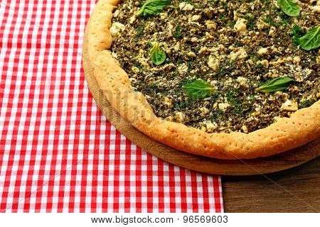 Open pie with spinach on table close up