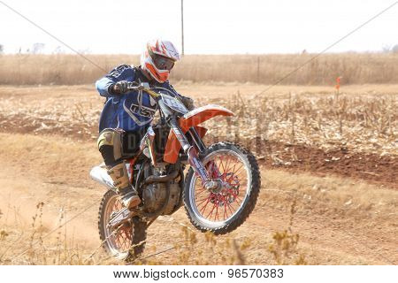 Motorbike Wheelie On Back Wheel Kicking Up Trail Of Dust On Sand Track During Rally Race.