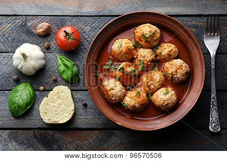 Meat balls with tomato sauce and ingredients on wooden background