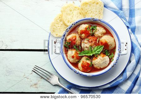 Meat balls with tomato sauce, on wooden background
