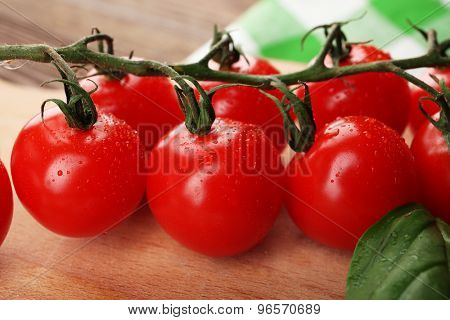 Fresh cherry tomatoes on wooden table, closeup