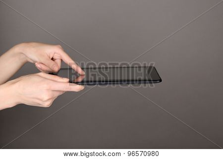 Female hands using tablet on gray background