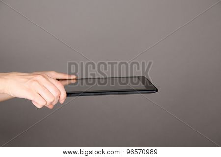 Female hand using tablet on gray background