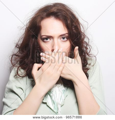 Beautiful young surprised curly woman. Studio shot.